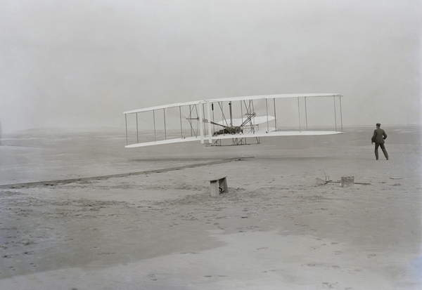 Wilbur Wright runs alongside as Orville pilots the aircraft just as it lifts from the wooden track at Kitty Hawk beach. It was the first powered controlled flight in a heavier-than-air airplane. December 17 1903 LC-DIG-ppprs-00626 / Everett Collection / Bridgeman Images 2938346