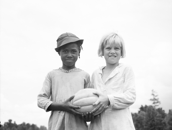 photo of Children at Hill House, Mississippi, 1936 (b/w photo), Lange, Dorothea (1895-1965) Daughters of former sharecroppers holding a melon on the Mississippi Delta Cooperative Farm in Hillhouse, Mississippi for their 4th of July celebration © Bridgeman Images