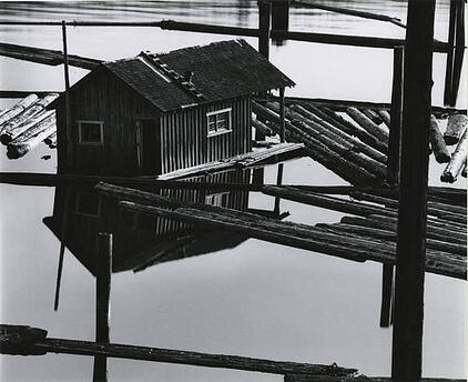 a monochrome phorograph of a log cabin floating on a lake, supported by wooden beams
