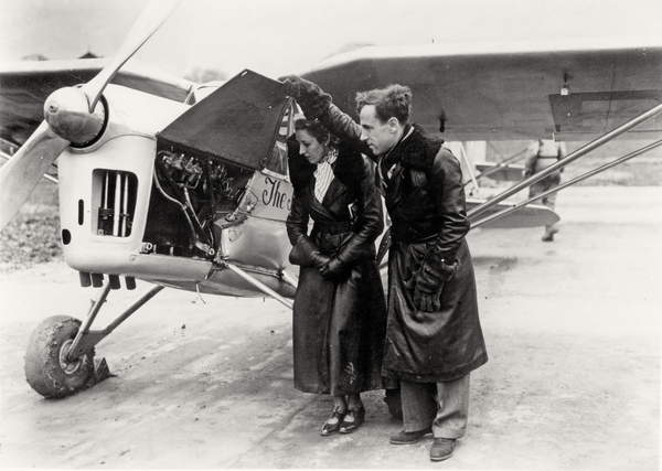 Amy Johnson (1903-41) and James Allan Mollison (1905-59) inspecting their plane (b&w photo), English Photographer, (20th century)  Private Collection  Bridgeman Images