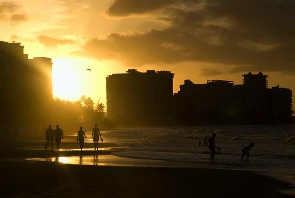 Puerto Rico, Carolina, silhouettes of people walking along beach at Isla Verde, sunset / Dorling Kindersley/UIG