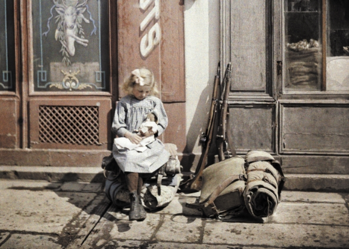 A little girl playing with her doll; two guns and a knapsack are next to her on the ground, Reims, Marne, France, 1917 (autochrome), Cuville, Fernand (1887-1927) / © Galerie Bilderwelt