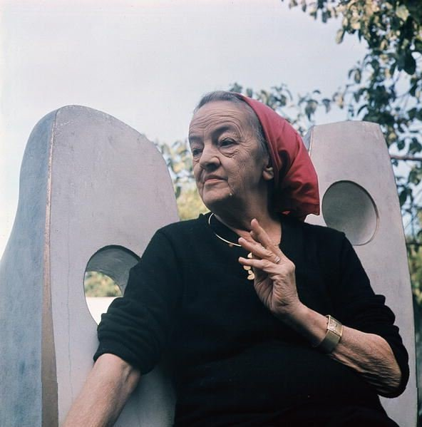 Portrait of Dame Barbara Hepworth (1903 - 75) seated in her garden next to one of her sculptures / Photo credit: Peter Kinnear